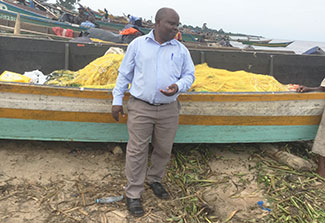 Dr. Joseph K.B. Matovu stands in front of a fishing boat on the shoreline in Uganda, many boats in the background.