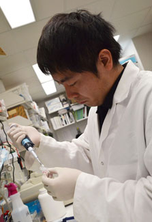 Japanese scientist Dr. Shogo Takahashi wearing white lab coat works in NIH lab with samples