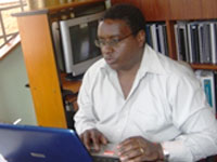 Dr. James Kiarie works on a computer seated at a desk