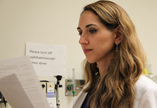 Dr. Laura Lewandowski reviews printouts in a medical exam room