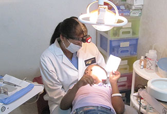 Dr Lilliam Pinzón performs a dental exam for a child in a reclined dental chair