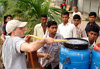 In Dhaka, Dr. Eric Nelson pumps water through a hose from a pond into a blue barrel, surrounded by others who are helping