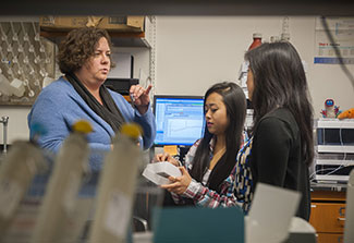 Dr. Marcy Balunas trains two female researchers in a lab