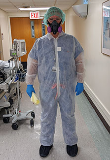 Dr. Mark Brady stands in the hallway of a hospital wearing full PPE, including a hair net, half-mask respirator, suit gloves.