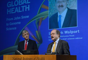 Sir Mark Walport speaks at a podium, NIH Director Francis S Collins looks on, slide reading global health projected
