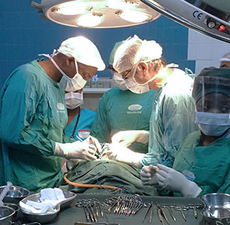 Dr. Matchecane Cossa performs surgery on a patient in an operating theater with 4 other medical workers.