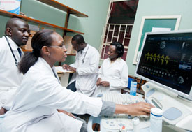 Medical workers in white coats, one adjusts computer with large monitor