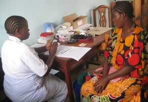 Woman medical worker enters data on smartphone while seated across table from a female patient