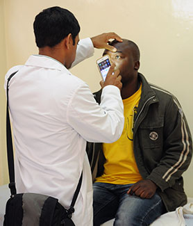 Medical worker examines patient's eye in exam room using smartphone.