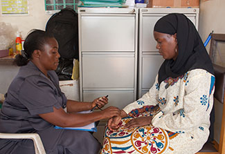 A medical worker takes the pulse of a patient in a clinic.