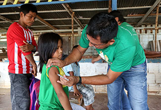 Medical worker gives girl a shot in her arm in Brazil