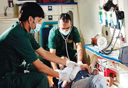 Two medical workers in an organized ambulance work with an injured patient reclined on a mobile stretcher.
