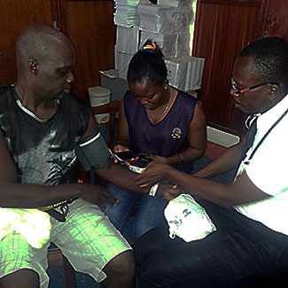 Two medical workers take blood pressure of adult male patient