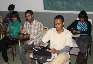 Five students seated in a classroom, all using tablet computers