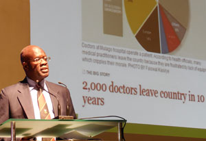 Dr. Nelson Sewankambo speaks into microphone at podium, slide reads 2,000 doctors leave country in 10 years