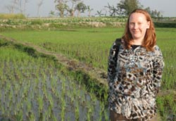 Dr. Juliet Pullium  stands in front of a field