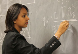 Dr Shweta Bansal intently works a complex math problem with chalk on a blackboard