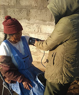 Health worker heavy coat takes the blood pressure of a seated woman.