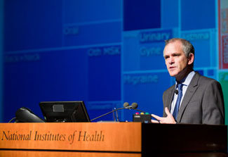 Dr. Christopher Murray speaks at a podium at NIH, slide of data visualization projected in background