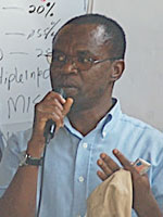 Fred Nalugoda speaking into microphone, gestures with hands