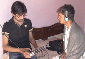 Young male researcher conducts hearing test on young man, who is seated on bed wearing earphone connected by chord to device