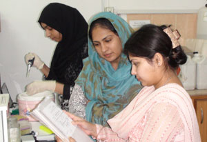 Dr. Sadaf Naz works in lab with two other women researchers, observing notes