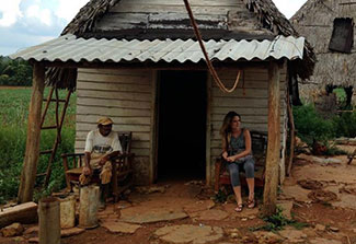 Older man and younger student seated in front of small farm house in Cuba