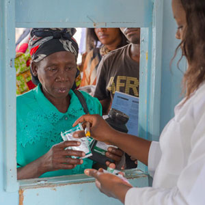 Medical worker in white coat distributes medications through a service window to an older woman