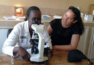 In lab Dr. Wendy Prudhomme O'Meara helps Kenyan researcher, who is looking in a microscope