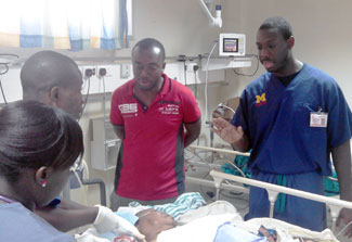 Dr Rockafeller Oteng speaks with others standing at bedside of a patient in a hospital bed