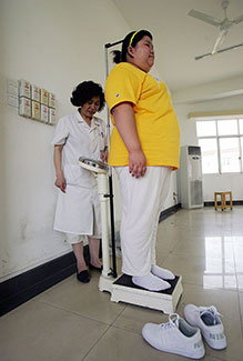 A child is being weighed by a medical worker at a base of the Aimin Slimming Centre in Wuhan of Hubei Province, China.