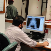 Male doctor examines x-ray on a computer monitor at desk in hospital
