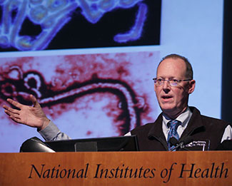 Paul Farmer speaking at a podium at NIH, slide projected in the background
