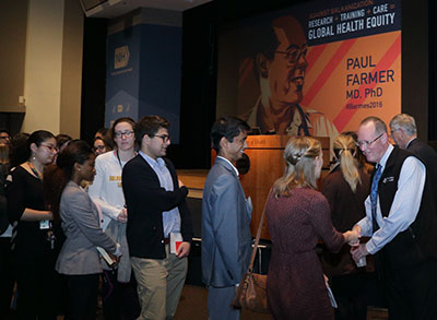 Paul Farmer shakes hands with a long line of attendees following a talk at NIH