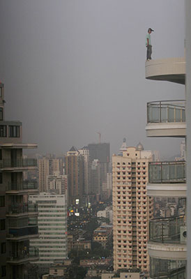 Person stands precariously on edge of balcony on very high floor of tall building, city skyline with tall buildings in background