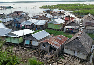 Homes in the slums in Peru built on logs adjacent to river.