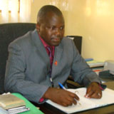 Dr. Sam Phiri seated at a desk