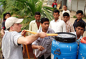 In Dhaka, Dr. Eric Nelson pumps water through a hose from a pond into a blue barrel, surrounded by others who are helping.
