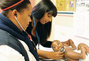 Dr. Bhakti Hansoti and healthcare worker examine infant using a stethoscope
