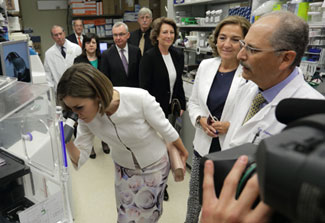 Queen Letizia of Spain peers into microscope while touring lab in NIH clinical center, NIH and Spanish leadership look on
