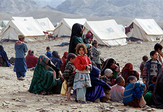 Group of Afghan refugees seated outdoors in a camp with tents in the background.