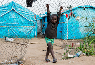 Young boy hangs on a chain link fence in front of tents in a refugee camp.