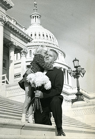 Historical photo of Rep. John E. Fogarty hugging a young girl on the outdoor steps of the US capitol building