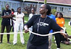 African woman in foreground in athletic wear holds rope, whistle around her neck, more women in background also wearing athletic