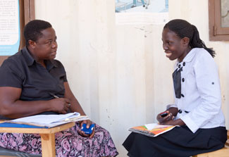 Female researcher collects data with pen and paper from female research participant who is seated across from her