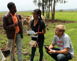 Two researchers collect data on tablets while speaking with a man in front of a field on a farm, cow in background