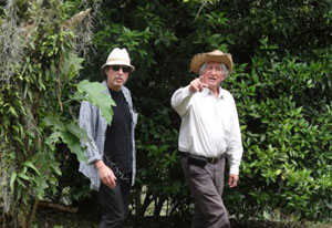 Dr Kenneth Kosik walks and talks with Colombian scientist Dr Francisco Lopera in a lush green wooded area