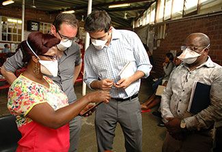 Researchers wearing surgical masks collaborate around a mobile device