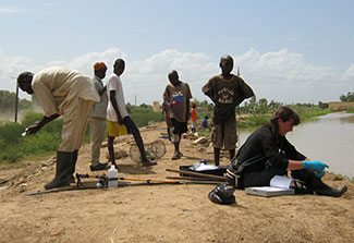 In Senegal, six researchers, some wearing gloves and boots, standing and seated on dry ground next to calm body of water.