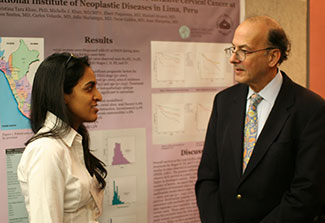 Early-career female researcher discusses her poster with Fogarty Director Dr. Roger I. Glass.
